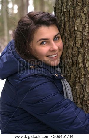 Beautiful Girl In A Blue Jacket Hugs A Tree And Smiles. Iceland Rangers Advised Hugging Trees While
