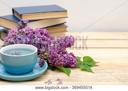 Books, A Cup Of Blue Tea From The Clitoris And Lilac On A Wooden Window. Fragrant And Romantic Conce