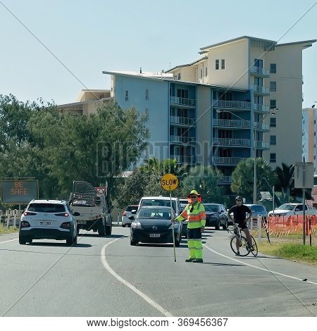 Mackay, Queensland, Australia - June 2020: Worker Holding Slow Sign To Control Traffic During Roadwo