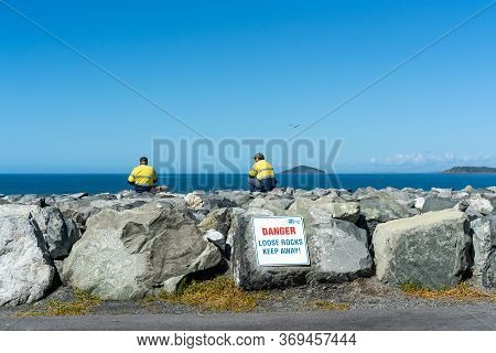 Mackay, Queensland, Australia - June 2020: Two Workers Taking A Break With Their Fishing Rods On Har