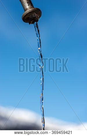 Extreme Close-up Of Fresh Water Flowing From An Outdoor Faucet On A Clear Blue Sky In Mountain (ital