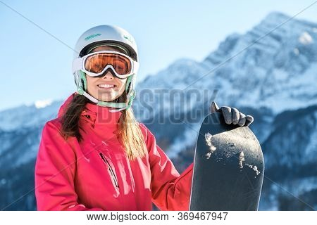 Woman Snowboarder Standing With Snowboard. Closeup Portrait Of Cheerful Snowboarder At Top Of Ski Sl