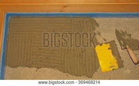 The Corner Of A New Concrete Floor In A Wooden House. Floor Tiling Adhesive Is Being Applied Ahead O