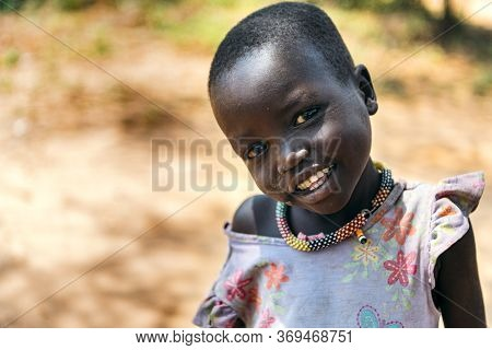 Boya Tribe, South Sudan - March 10, 2020: Small Girl In Colorful Dress And Traditional Necklace Smil