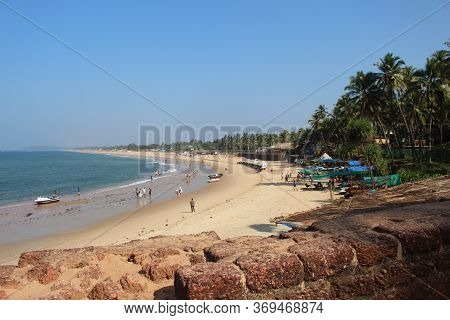 Goa, India-january 7, 2017. People Walk Through The Beach Sinquerim Along The Coastline. Tourists An