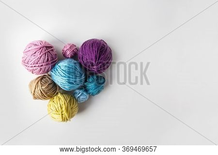 Multicolored Wool Skeins In Heart Shape On Light Background. Copy Space. Top View. Knitting As Lovel