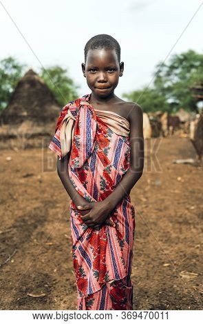 Toposa Tribe, South Sudan - March 12, 2020: Girl Wrapped In Floral Fabric Looking And Camera And Smi