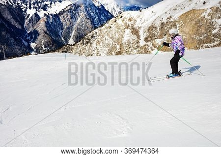 View From Side On Young Girl Ski Fast Downhill On Winter Resort