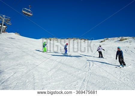 Four Kids Ski Downhill In Alpine Slope In School Formation Together One After Another