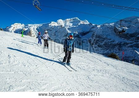 Four Kids Ski Downhill In Alpine Slope In School Formation Together One After Another Moving In Came