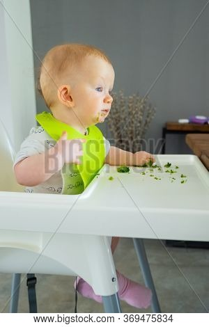 Sweet Baby Making Mess While Eating Broccoli Vegs. Little Child Wearing Plastic Bib, Sitting In High