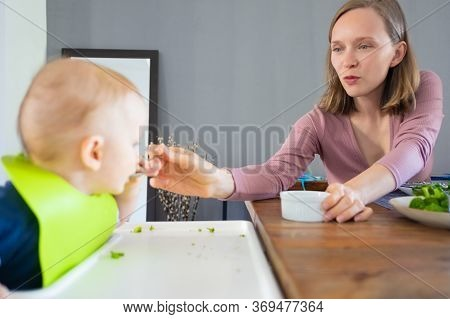 Happy New Mom Feeding Baby Daughter With Spoon. Little Child Wearing Plastic Bib, Sitting In Highcha