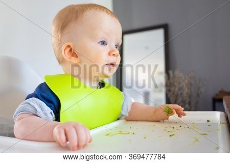 Excited Baby Looking Away While Eating Broccoli, Training To Eat By Herself. Little Child Wearing Pl