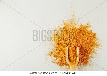 Turmeric Powder In Wood Spoon On Gray Background