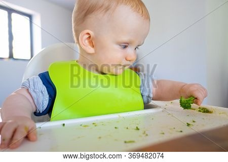 Adorable Baby Learning To Eat By Herself, Taking Piece Of Green Vegetable, Eating Broccoli. Little C