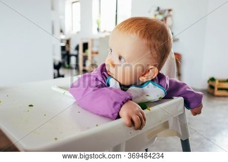 Portrait Of Curious Little Child Sitting On Highchair Messy After Feeding. Baby Girl Wearing Bib Sit