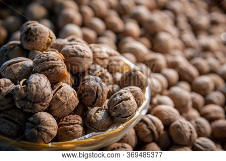 Bunch Of Fresh Walnuts In A Wicker Bowl For Sale On A Street Market In China