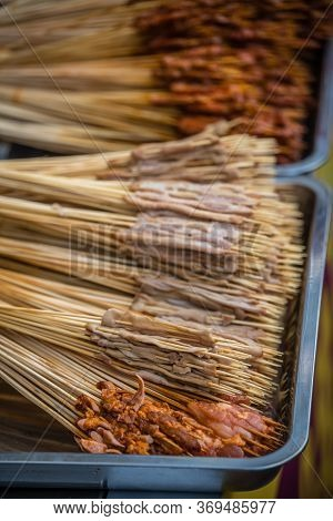 Portions Of Raw Meat, Vegetables And Seafood On Wooden Sticks, Ready To Be Grilled On The Street In