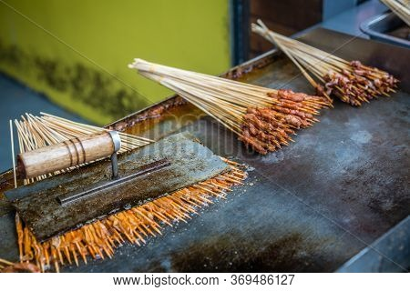 Portions Of Raw Meat, Vegetables And Seafood On Wooden Sticks Cooked And Fried On A Hot Plate On The