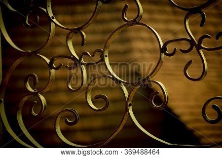 Detail Of A Wrought Iron Fence Illuminated By The Rays Of The Setting Sun.