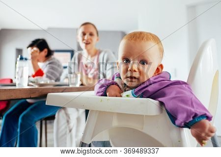Portrait Of Cute Baby Girl Sitting At Table With Mom And Granny. Little Child Wearing Bib Having Bre