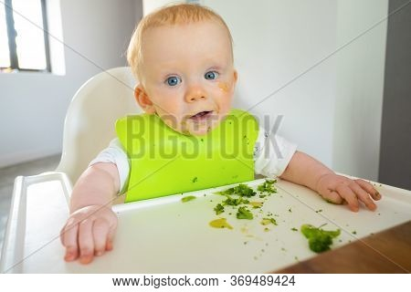 Positive Baby Having Lunch With Broccoli Vegs, Making Messy On Tray, Looking At Camera. Little Child