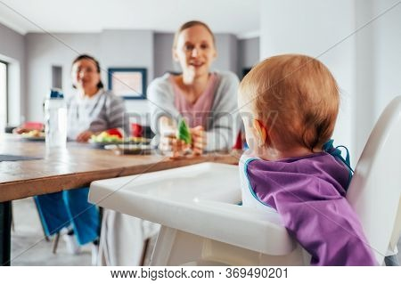 Young Mom Feeding Her Child With Solid Food In Dining Room. Cute Baby Girl Sitting On Highchair And