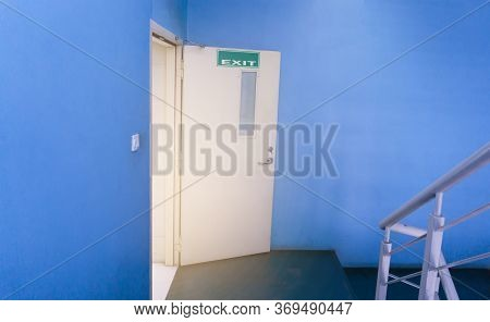 A Cream Fire Exit Door Opened From A Blue Wall Room To A Stair With Gray Color Railing, A Green Sign
