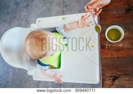 Above View Of Baby On Highchair Refusing Spoon With Soup. Little Child Eating Puree With Help Of Her