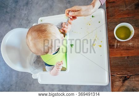 Mother Feeding Baby Girl With Puree. Above View Of Little Child Sitting On Highchair And Eating With