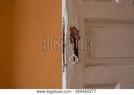 Close Up Of A White Painted Old Damaged Wooden Door Of An Empty Abandoned Old Building.