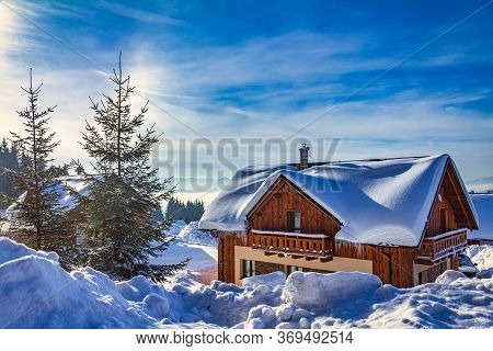 Winter Landscape With A Snow-covered Wooden Mountain Hut.