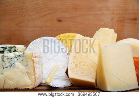 Closeup Of Various Cheeses Laying On Wooden Board. Edam, Gouda, Cheddar. Studio Shot. Side View. Dai