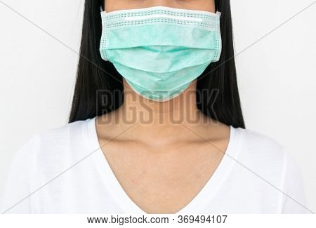 Surgical mask.  A woman wears a face mask that protects against the spread of Coronavirus (COVID-19).