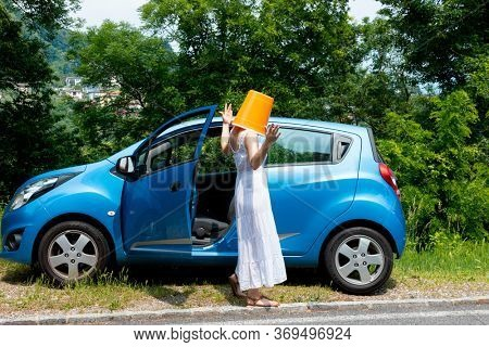 Woman with an orange bucket on her head gets out of the car because of a breakdown. She is surprised and not happy