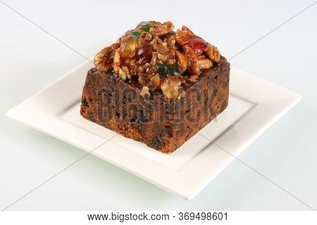 A Small Rich Fruitcake Photographed Against A White Background