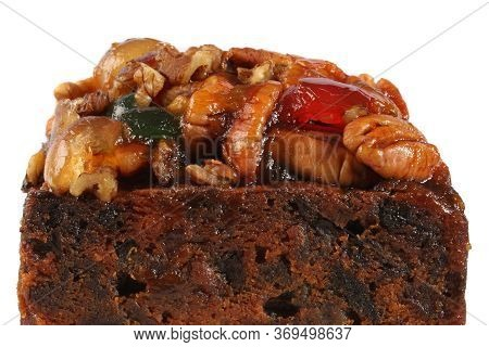 A Rich Fruitcake Photographed Against A White Background