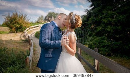 Toned Closeup Portrait Of Newly Married Couple Passionately Kissing On Field At Countryside