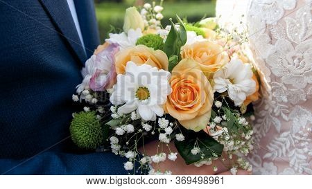 Closeup Image Of Newly Married Couple Holding Beautiful Wedding Bouquet