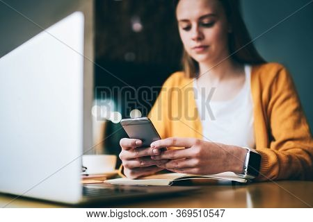 Young Freelancer Sending Messages On Mobile While Working On Project In Cafe