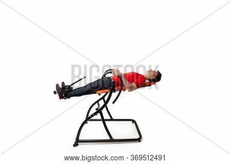 Man Doing Exercise On Inversion Table For His Back Pain, Isolated On White