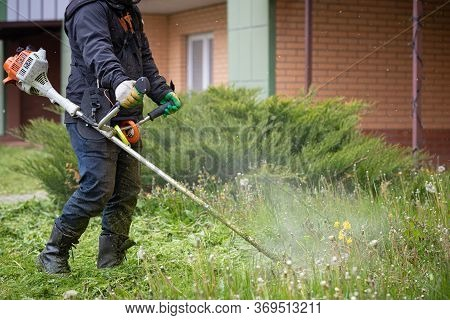 A Man With A Lawn Mower On A Grassy Field Near The House. A Man In Protective Clothing, Gloves And R