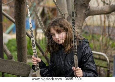 Girl 10 Years Old Swinging On A Swing In The Spring. A Teenager In A Black Jacket On A Swing. Swingi