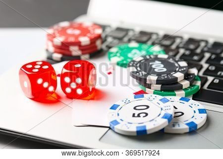 Online Poker Casino Theme. Gambling Chips With Dice And Playing Cards On Laptop.