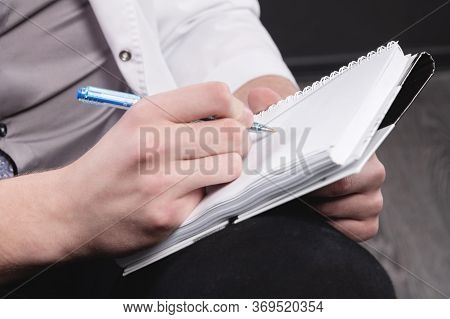The Mens Hands Of A Psychologist Doctor In A White Robe Hold A Notebook And A Ballpoint Pen With A N