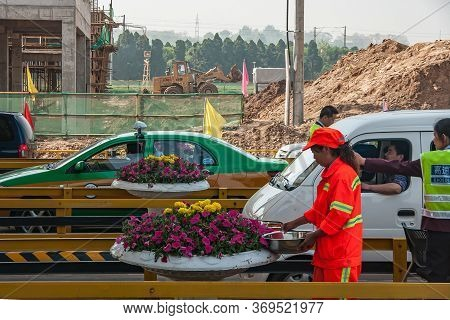 Xian, China - May1, 2010: Woman In Hell Red Security Garb Waters Pot Of Flowers While Cars Pass Thro