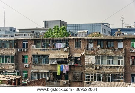 Xian, China - May 1, 2010: Old Residential Brown Brick Housing With Dilapidated Balconies, Ac System