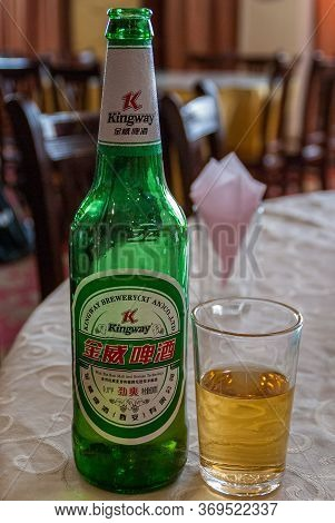 Xian, China - May 1, 2010: Closeup Of Green Bottle Of Kingway Brewery Beer With Yellow Pilsner Liqui