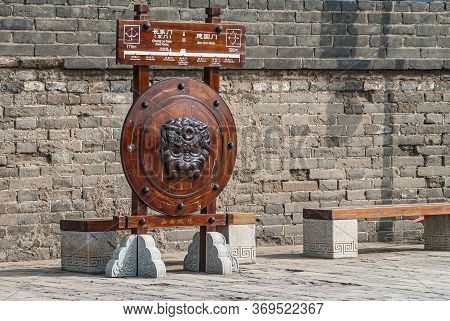 Xian, China - May 1, 2010: City Wall Brown Stone Ramparts. Sculptured Circular Wooden Shield With Be