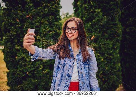 Half Length Portrait Of Positive Hipster Girl In Optical Eyeglasses Smiling At Camera
